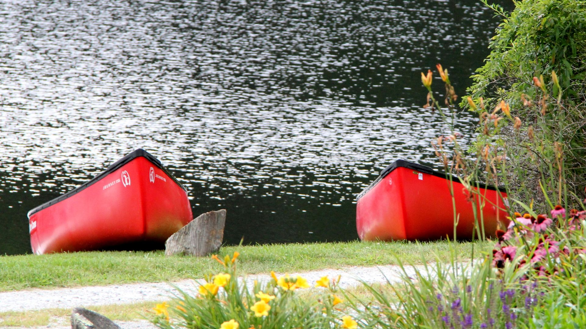 A Red And Yellow Boat Sitting In The Grass
